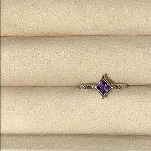 Silpada ring with purple crystal and side designs.